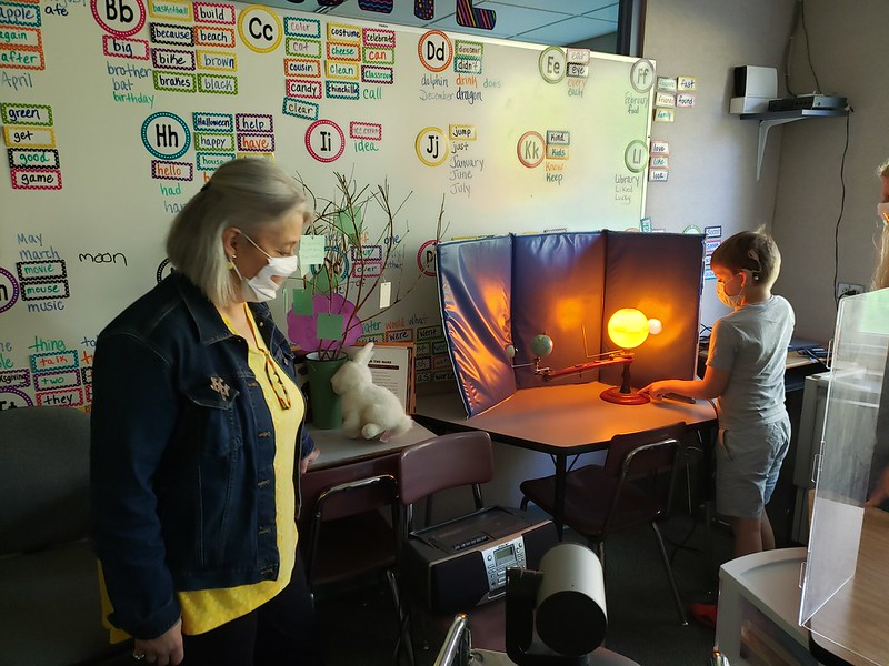 Judy, Clarke's Chief Program Officer, views a student's science project
