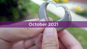 Hands holding hearing aids in shape of heart